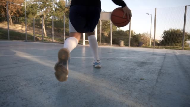 Rare view of a young girl basketball player training and exercising outdoors on the local court. Running with the ball, bouncing and make a shot. Low angle footage