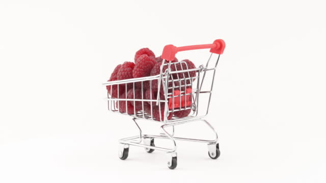 Raspberries in mini toy trolley. Close-up, isolated, on white background. Copy space. Summer juicy berry