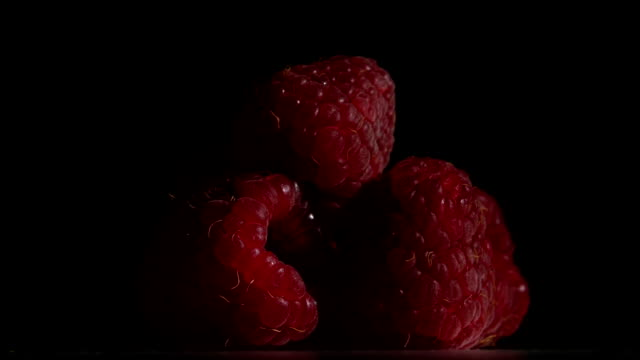 Raspberry fruit is revolve on a black background. Close up video
