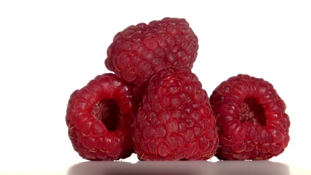 Raspberry fruit is revolve on a white background. Close up video