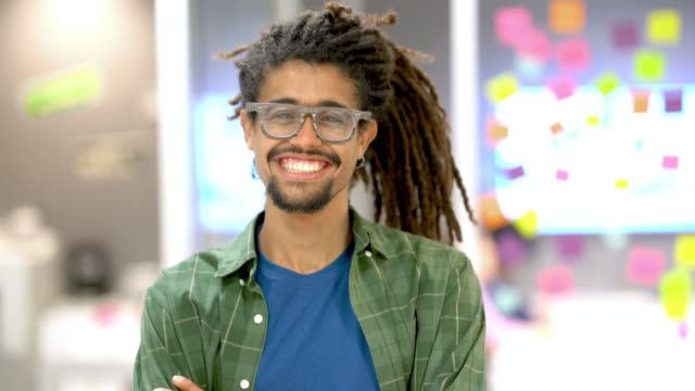 vídeos y material grabado en eventos de stock de hombre joven rasta caminando de la sala de juntas a la cámara con los brazos cruzados sonriendo en la oficina - toma mediana
