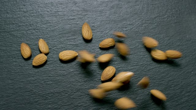 Raw Almonds on Slate in Slow Motion video