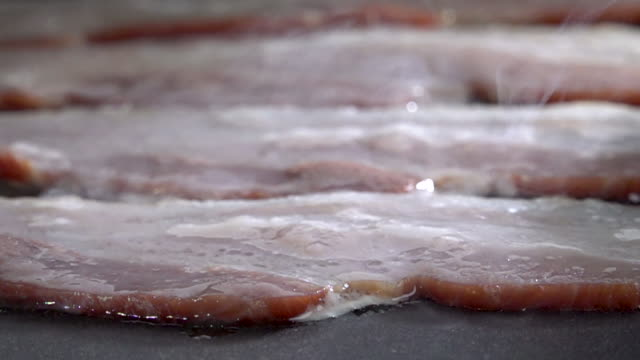 Raw Bacon on the Griddle In Slow Motion video