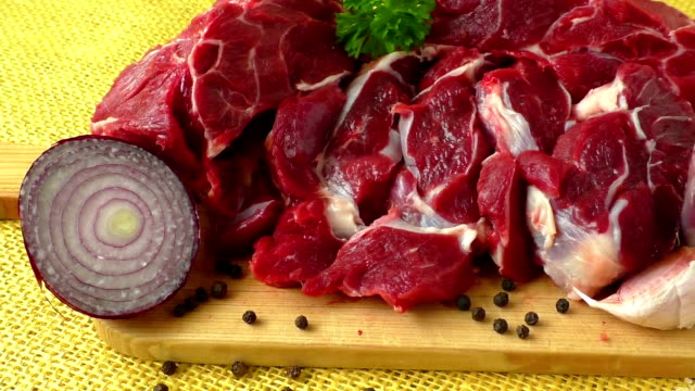 Raw beef on wooden board with garlic and onions video