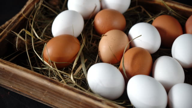 Raw eggs with straw in a wooden box.