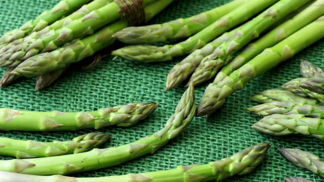 Raw garden asparagus stems. Fresh green spring vegetables on green jute background. (Asparagus officinalis) video