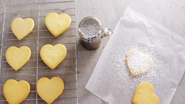Raw heart shape cookies on baking tray with flour shaker strainer and wax paper 4k video