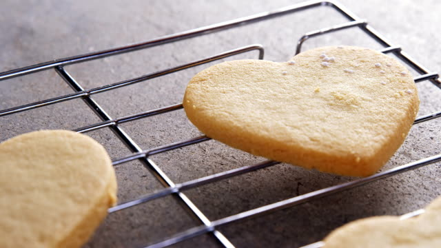 Raw heart shape cookies with sugar icing on baking tray 4k video