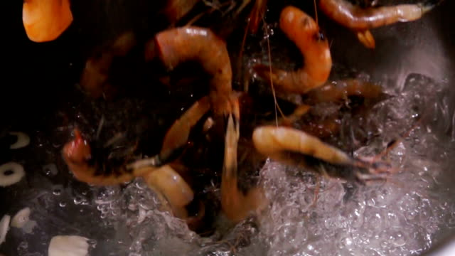 raw large prawns fall into boiling water - crostaceo video stock e b–roll