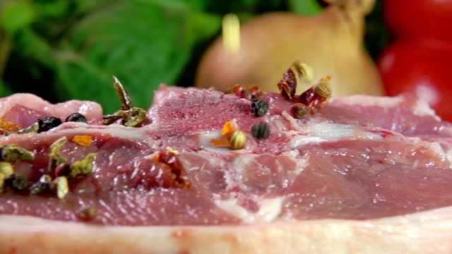 vídeos de stock e filmes b-roll de raw meat sprinkled with spices and pepper - beef angus