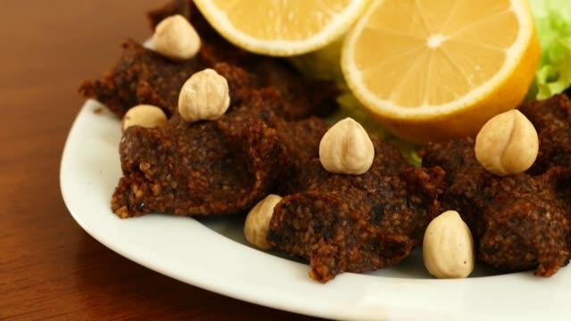 råa kött bullar med nötter, särskilda kryddig rå kalkon kött bullar, (çig köfte) - pinjenöt bildbanksvideor och videomaterial från bakom kulisserna