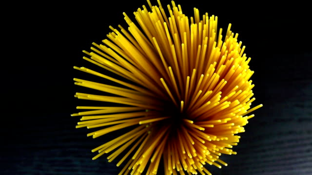raw pasta spaghetti on black wood table, typical italian cuisine top of view of bunch of raw pasta spaghetti on black wood table, typical italian cuisine 1080 HD uncooked pasta stock videos & royalty-free footage