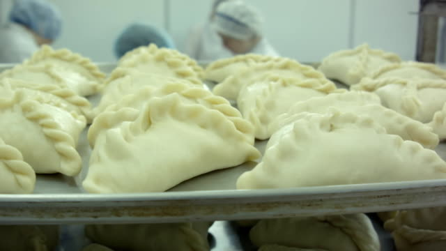 raw pastry dough with meat in the background preparing the blurry women