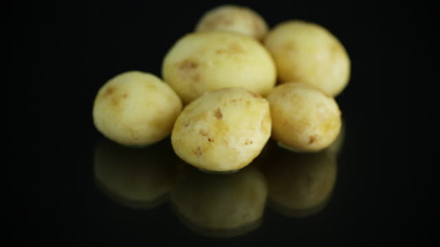 raw peeled early potato on black background video