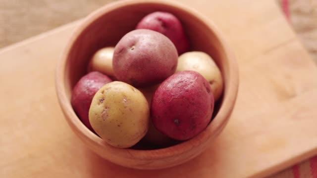 Raw potato in wooden bowl, close-up Raw potato in wooden bowl at rotating stand. Steadicam close-up red potato stock videos & royalty-free footage
