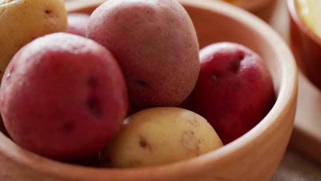 Raw potato in wooden bowl, steadicam close-up Raw potato in wooden bowl at rotating stand. Steadicam close-up red potato stock videos & royalty-free footage