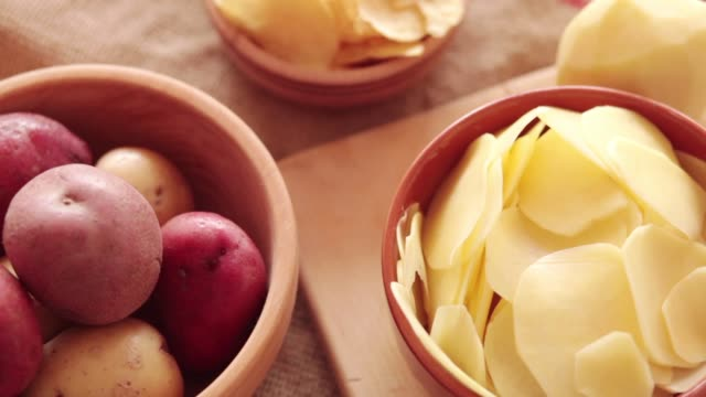 Raw potato, potato chips, shot from above, close-up Raw potato in wooden bowl with chips and thin slices at rotating stand. Steadicam Close-up, no people. red potato stock videos & royalty-free footage