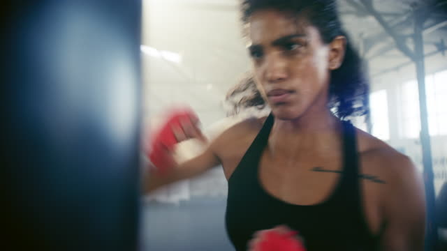 Raw punching power 4k video footage of an attractive young female kickboxer practising in the gym martial arts stock videos & royalty-free footage