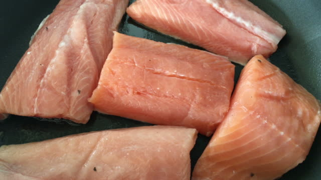 Raw Salmon Fish Fillets Cooked on a Frying Pan Slice of raw Salmon Fish fillets cooked on a frying pan. roast dinner stock videos & royalty-free footage