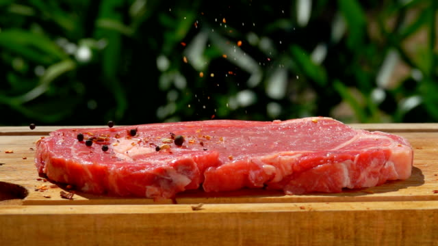 A raw thick meat steak is sprinkled with spices on the wooden board A raw thick meat steak is sprinkled with spices on the wooden board on the background of greenery outdoors seared stock videos & royalty-free footage