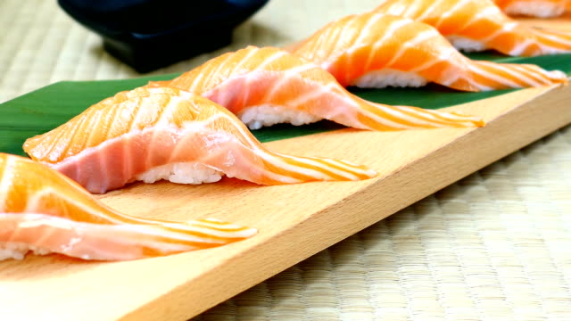 vídeos de stock, filmes e b-roll de cru com salmão fresco peixe sushi de carne no tabuleiro de madeira - estilo de comida japonesa - sushi
