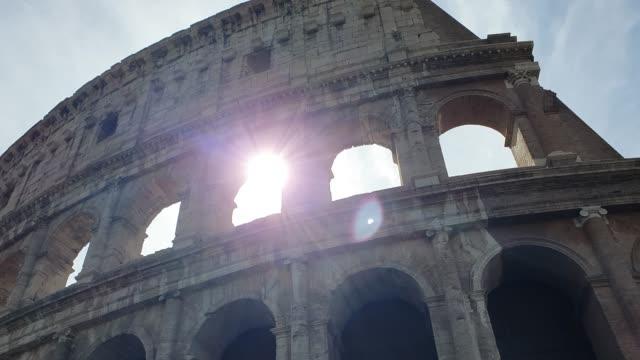 a ray of sun passes through the arches of the colosseum in rome, italy. - stile classico romano video stock e b–roll