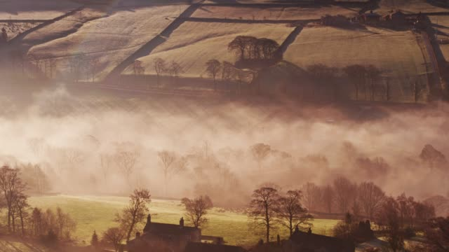 rays of sunlight on morning fog - drone shot - england stock videos & royalty-free footage