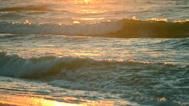 Rays of the setting or rising sun with sea waves on the shore close up