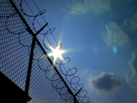 Razorwire Big Pan Big sky and sun with razorwire fence, pan, PAL sentencing stock videos & royalty-free footage