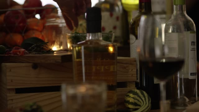 vídeos de stock e filmes b-roll de reaching for a green bean on side table at a party with wine, brandy and snacks - elegante