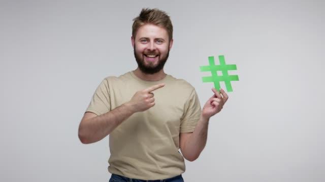 vídeos de stock, filmes e b-roll de leia a mensagem marcada! cara barbudo alegre apontando símbolo hashtag, sorrindo para a câmera, mostrando hash - tag