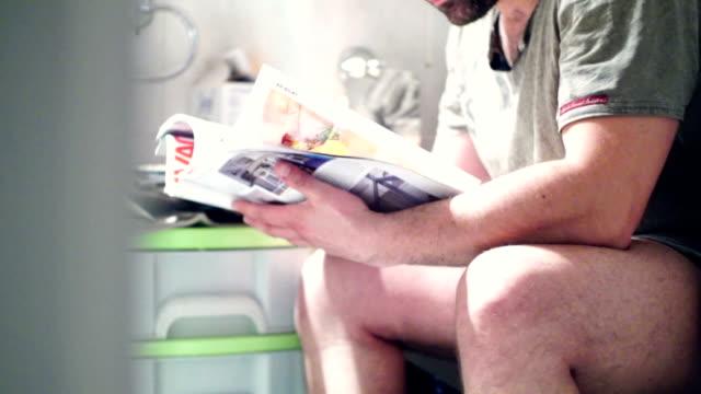 Reading a magazine in bathroom. video