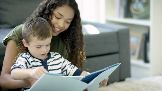 Reading a Storybook A female mixed-race teenage babysitter and a Caucasian boy of pre-school age are sitting together in a living room. The teenage girl is helping the boy read a storybook. child care stock videos & royalty-free footage