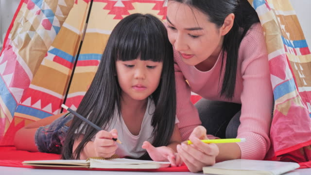 reading and family games in children's tent. mother and child daughter with book before going to bed - parenting video stock e b–roll