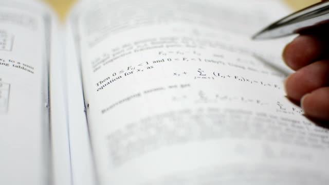 Reading exam preparation books. video