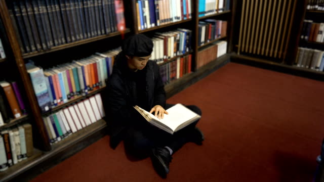 Reading Historic Book in Old Library While Sitting on Floor