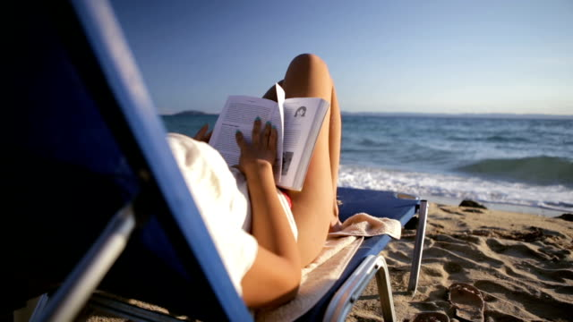 Reading on the beach Beautiful woman reading on the beach sunbathing stock videos & royalty-free footage