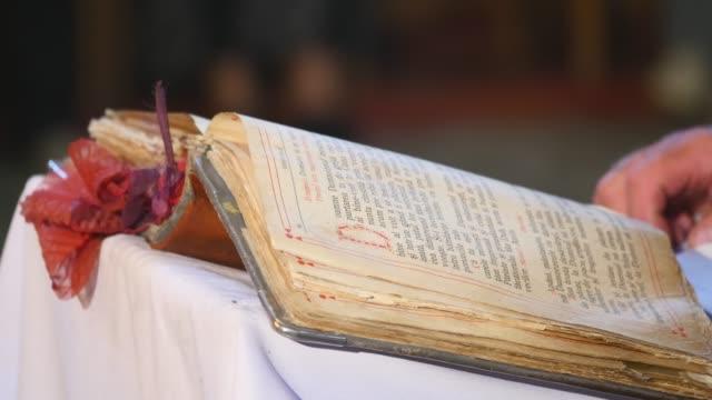 vídeos de stock, filmes e b-roll de leitura do santo evangelho. sacerdote ortodoxo de mãos vira a página - batismo