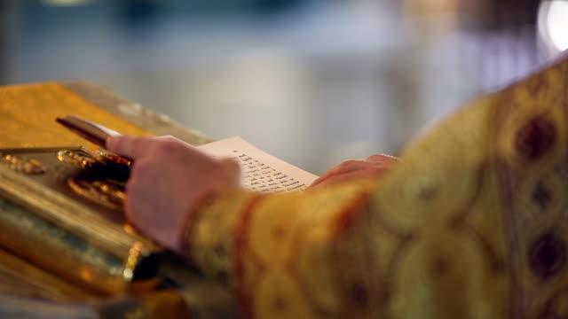 vídeos de stock, filmes e b-roll de leitura o santo gospel. mãos ortodoxa padre s'a página - batismo