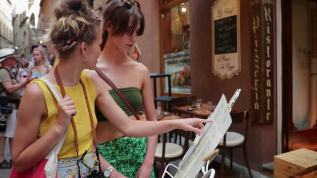 Reading the Menu Female couple are looking at a menu outside of a restaurant in Volterra, Italy. menu stock videos & royalty-free footage