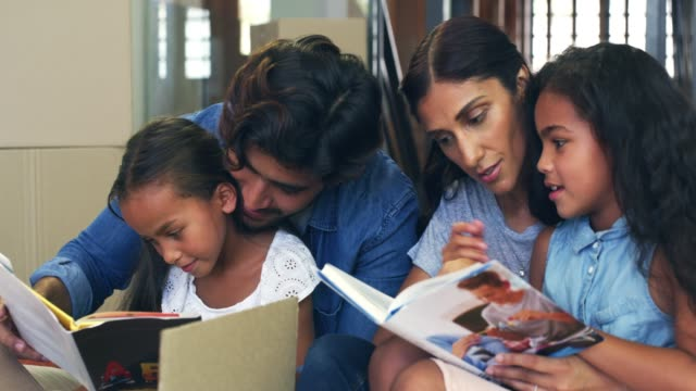 Reading time is important in our household 4k video footage of a young family reading books together while unpacking in their new home indian family stock videos & royalty-free footage