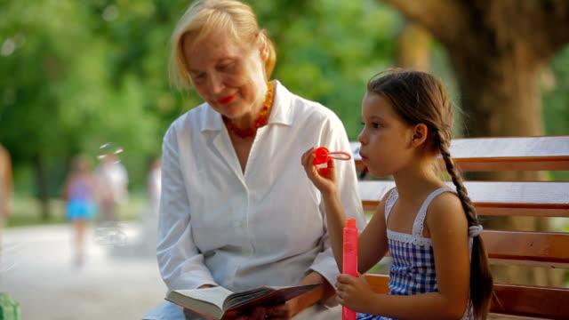 nipote di lettura - nonna e nipote camminare video stock e b–roll