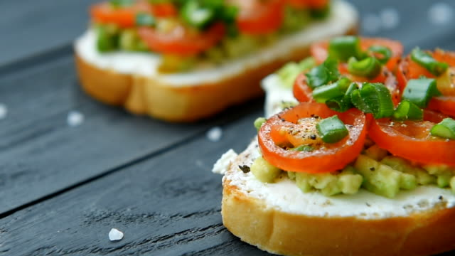 ready bruschetta with cream cheese and chopped veggies - avocado video stock e b–roll
