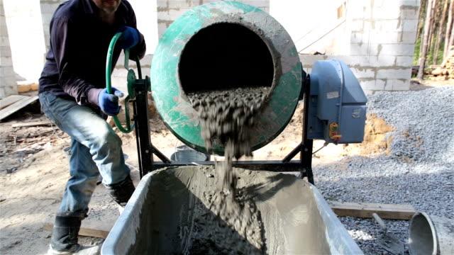 Ready concrete pours out of the concrete mixer into the wheelbarrow. video