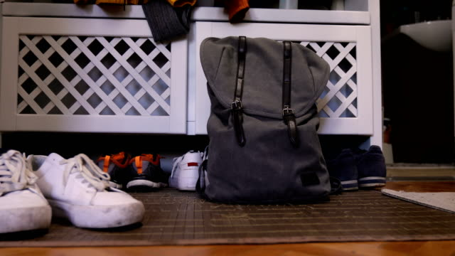 Ready to go Backpack, sport shoes and shoe rack with family storage space for shoes in domestic home mud stock videos & royalty-free footage