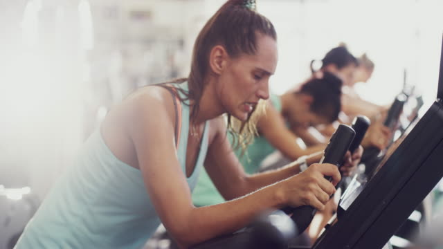 Ready to transform their bodies 4k video of people working out on an elliptical machine at the gym health club stock videos & royalty-free footage