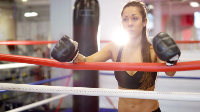 real and powerful woman rests after workout in boxing ring - kick boxing video stock e b–roll