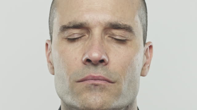 Real caucasian adult man closing eyes Slow motion close up video portrait of spanish young man closing eyes at camera. Footage of real caucasian man against gray background. Studio 4K RAW video with sharp focus on eyes. eyes closed videos stock videos & royalty-free footage