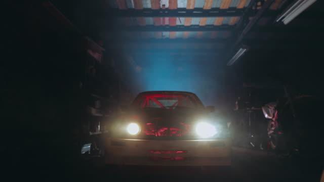 echte klassische oldtimer in futuristischer garage. - garage stock-videos und b-roll-filmmaterial