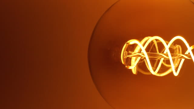 Real Edison light bulb flickering. Vintage filament Edison light bulb. Close up Edisons Vibrating Filament Yarn. Incandescent lamp in antique style. tungsten image stock videos & royalty-free footage
